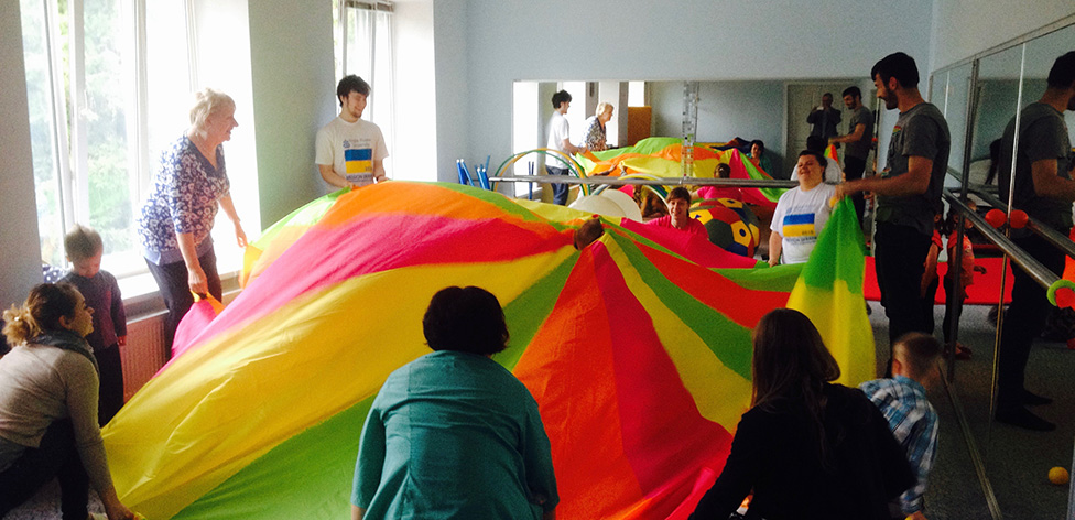 The team playing with children under the parachute