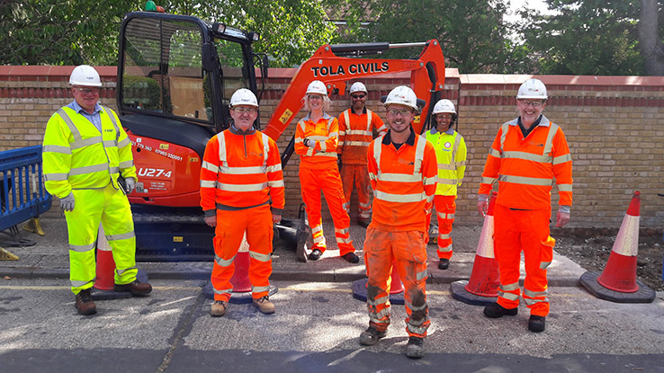 Staff from Ringway Jacobs and ARU in front of a digger, wearing high-viz suits