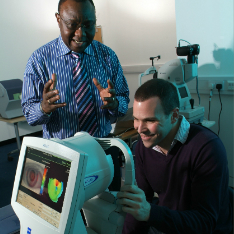 two men performing eye testing while showing eye curvature exam results on screen