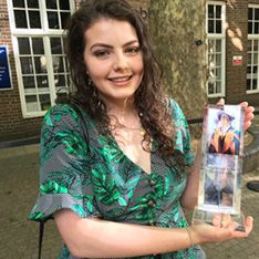 Ashleigh Robinson in grey and green summer dress holding the Supanee Gazeley prize