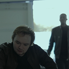 Still from a film: one actor seated, another actor approaching him from behind