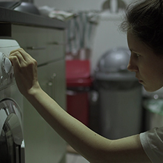 Film still: woman turning the dial on a washing machine