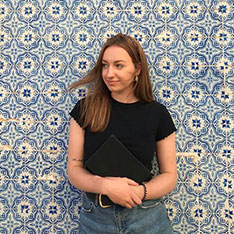 Student Lizzie Knott standing against a blue and cream tiled wall