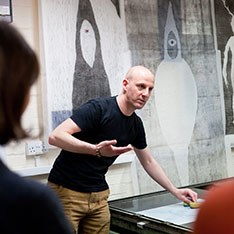 John Williams demonstrating print equipment, with prints on wall behind
