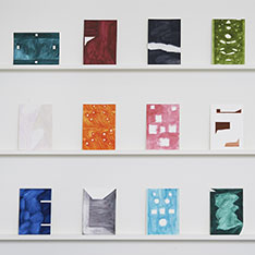 Twelve abstract works in various colours displayed in three rows of four on wall shelves