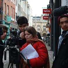 Film maker Solomia Dzhurovska in red jacket with a crew of three filming on Cambridge street
