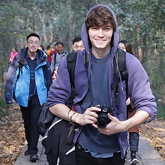 Stefan Tomov, holding camera, wearing purple hoodie, with other members of group behind in woodland
