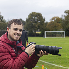 Head shot of Tom Alfuth in red jacket, holding camera with long lens, on the side of football pitch