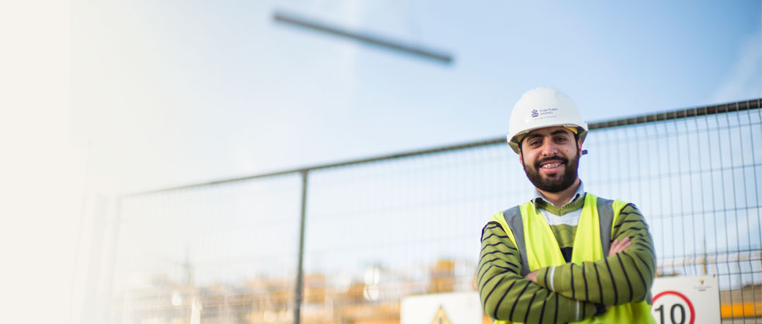 Construction student in front of a building site