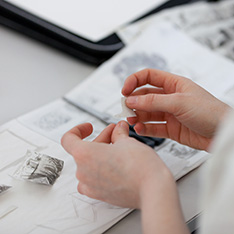 Close-up of person sticking small drawings into a sketchbook
