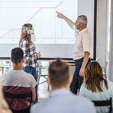 A man and woman work on an interative whiteboard in front of an audience