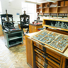 Printing presses and type drawers in a printmaking studio