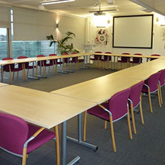 Corporate suite set up with a rectangle of tables and chairs