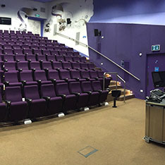 Lecture theatre with rows of purple chairs from the front at an angle