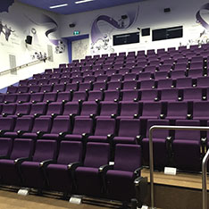 Lecture theatre with rows of purple chairs from the front