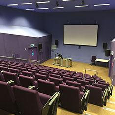 Lecture theatre with rows of purple chairs from the back