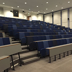 Lecture theatre with rows of straight desks taken at an angle