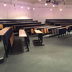Lecture theatre with rows of straight desks and lighting