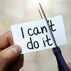 Person cutting piece of paper with the words 'I can't do it' on it - removing the 't'