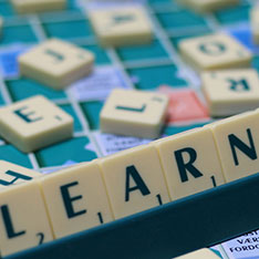 Scrabble titles spelling out the word 'learn'