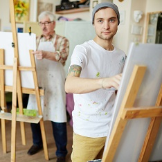 People taking part in an art class, painting on easels