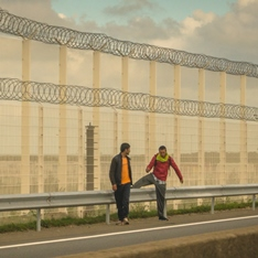 Two men by a fence at the port of Calais