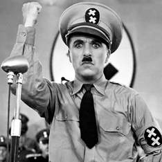 Charlie Chaplin, in The Great Dictator, dressed in a military uniform with his fist held up in the air