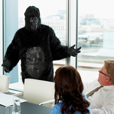 Person in a gorilla suit addressing workers in an office meeting room.