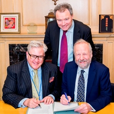 Three men signing a piece of paper