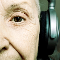 An older person wearing headphones