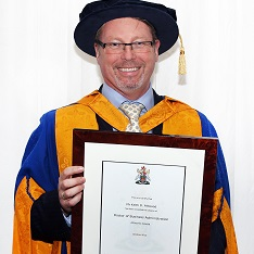 Keith Attwood holding his honorary degree certificate from ARU