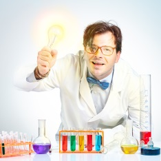 A scientist, wearing a lab coat and surrounded by test tubes and beakers, holds up a light bulb.