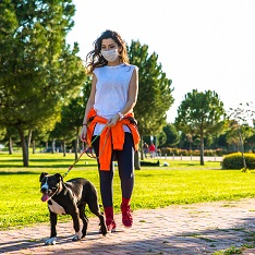 Woman wearing mask walking dog