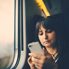 A woman using a smartphone on a train