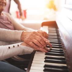 An older person playing the piano