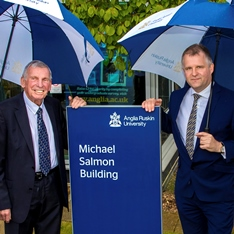 Professor Michael Salmon and Professor Iain Martin standing next to a sign that says 'Michael Salmon Building'