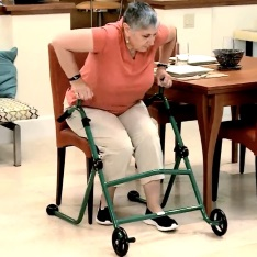 A woman using a rise-up walker to get out of her chair.