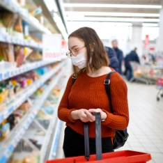 A woman in a supermarket wearing a mask