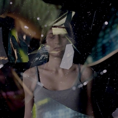 A young woman surrounded by glass shards