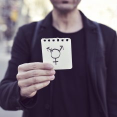 A person holding up a piece of paper with the transgender symbol on.