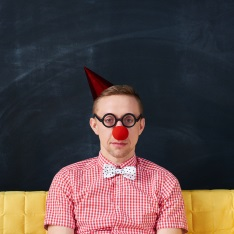 Straight-faced man wearing a clown nose and party hat