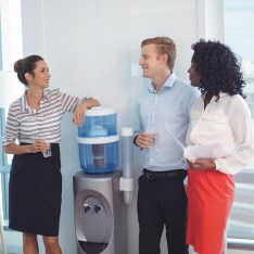 People stood next to an office watercooler