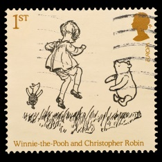 First class stamp featuring a sketch depicting Winning the Pooh, Christopher Robin and Piglet skipping on some grass.