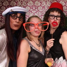 Three women in fancy dress and pulling funny faces in a photo booth.