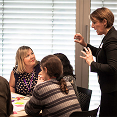 Woman talking to table of people at workshop