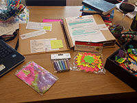 A picture of Lucie's desk filled with her laptop, notebook and stationery