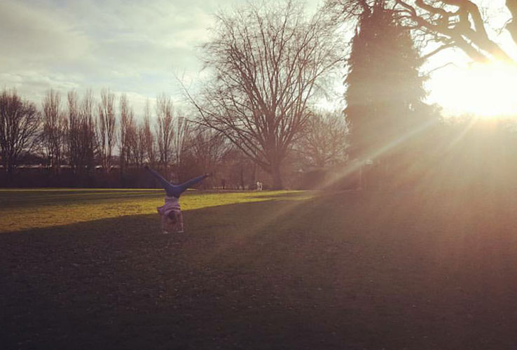 Sunshine through trees onto a park, with a person doing a handstand