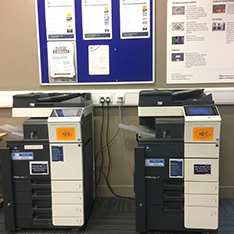 two photocopiers in front of a wall
