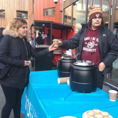 People at a stand containing kegs of mulled wine