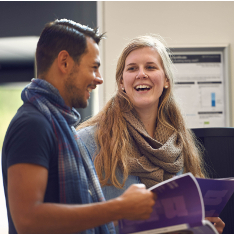 A young man and woman holding the ARU prospectus on campus